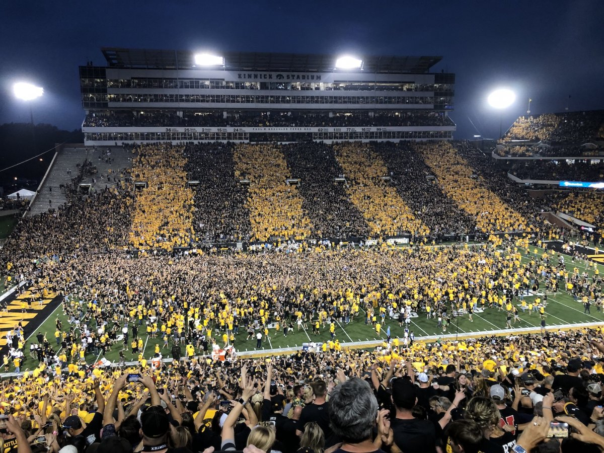 Students and fans rush the Kinnick Stadium field