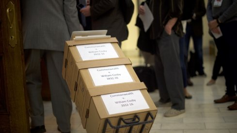 A lawyer pulls boxes of legal documents.
