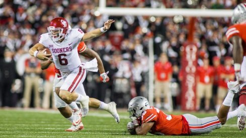 Oklahoma quarterback Baker Mayfield eludes an Ohio State defender