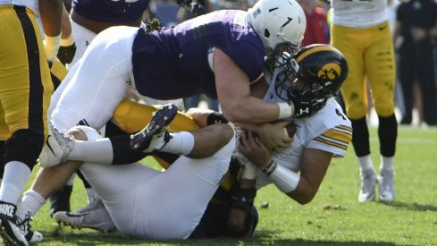 Iowa quarterback Nathan Stanley is tackled by a Northwestern defender.