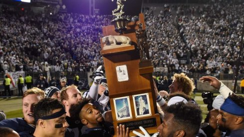 Penn State players hold the Land Grant Trophy