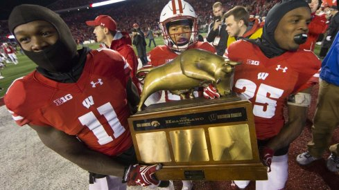 Wisconsin players carry the Heartland trophy after defeating Iowa