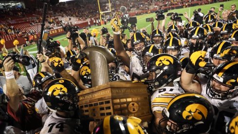 Iowa hoists the Cy-Hawk Trophy