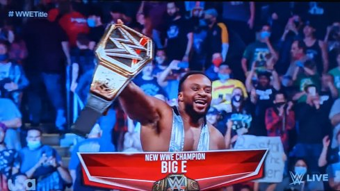 Big E holds up the WWE championship belt as fans stand and applaud him.